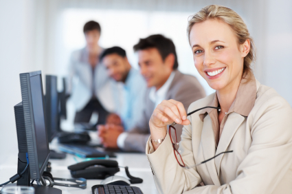 Business woman at work giving you an attractive smile with colleagues in background
